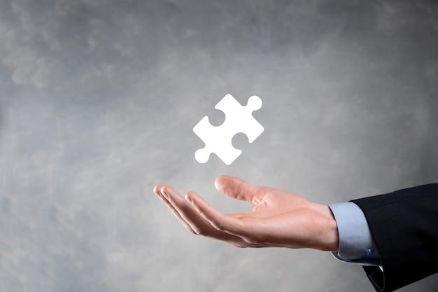 Mani dell'uomo d'affari che collegano i pezzi del puzzle che rappresentano la fusione di due società o joint venture