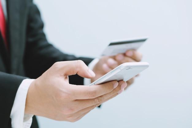 Mani dell'uomo d'affari che tengono la carta di credito e usando il telefono. acquisto in linea di acquisto vendita o pagamento.