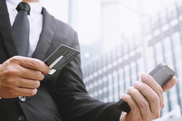 Mani dell'uomo d'affari che tengono la carta di credito e usano il telefono.