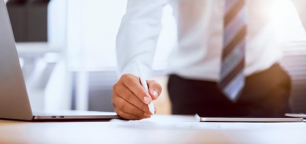 L'uomo d'affari passa la tenuta della penna digitale e la compressa usando con il computer all'ufficio. proporzione del banner per gli annunci.