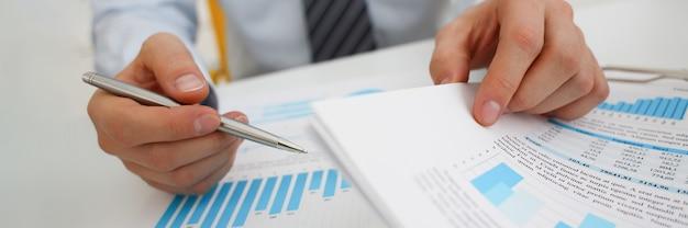 Mani dell'uomo d'affari che tengono la mano e grafici di affari commerciali. sviluppo e analisi della pianificazione delle piccole e medie imprese