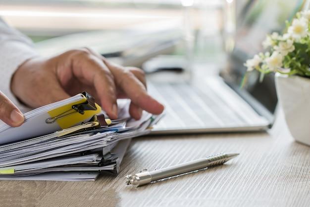 L'uomo d'affari passa la penna di tenuta per il lavoro nelle pile di archivi cartacei che cercano la relazione di attività di informazioni