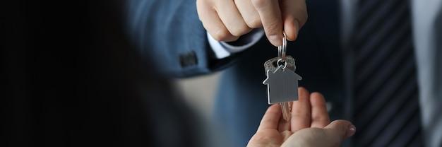L'uomo d'affari consegna le chiavi di casa al cliente
