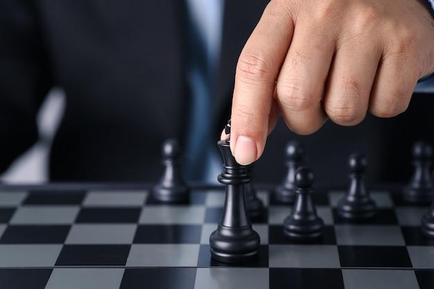 Mani dell'uomo d'affari che muovono il re degli scacchi alla posizione di successo sul gioco di affari della concorrenza