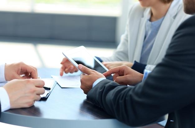 Mani dell'uomo d'affari che toccano lo spazio vuoto della copia dello schermo della compressa digitale, stretta di mano durante la riunione.