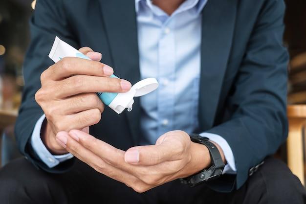 Mani dell'uomo d'affari che utilizzano il dispenser di gel disinfettante per le mani, contro la malattia da coronavirus (covid-19) in ufficio o in un bar. antisettico, igiene e concetto di assistenza sanitaria