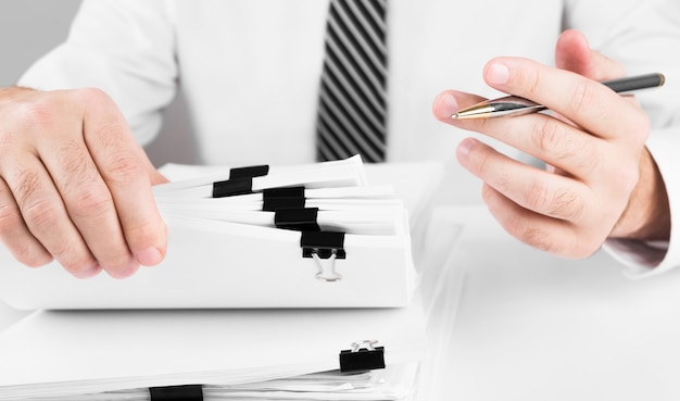 Mani di uomo d'affari che lavorano in pile di archivi cartacei per la ricerca di informazioni, affari e concetto finanziario.