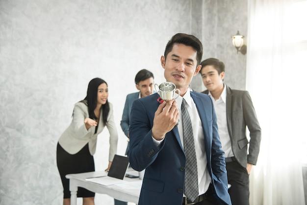 Uomo d'affari felice orgoglio con win cup e business team geloso dietro