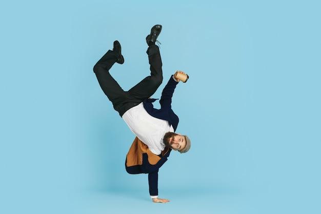 Uomo d'affari che si diverte a ballare break dance su sfondo blu al lavoro