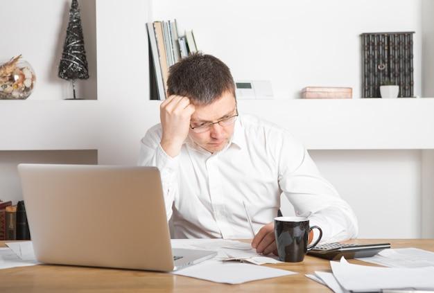 Uomo d'affari che ha sforzo con il computer portatile che lavora nell'ufficio, uomo caucasico che tocca la sua testa, sta avendo un mal di testa, uno sforzo e un concetto di lavoro eccessivo.