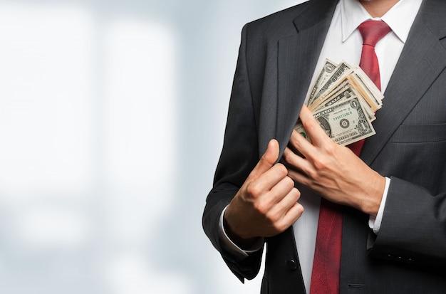 Uomo d'affari che nasconde banconote in dollari nella tasca della giacca
