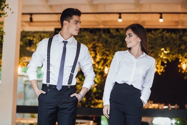 L'uomo d'affari e il suo assistente in camicie bianche in un ufficio moderno esaminano i documenti e discutono il lavoro