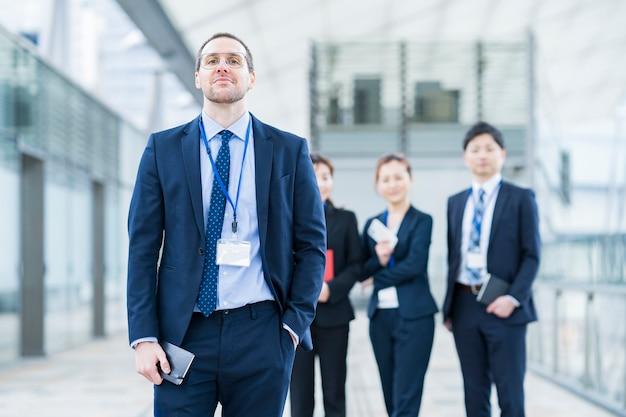 Uomo d'affari e il suo team aziendale in piedi in zona ufficio