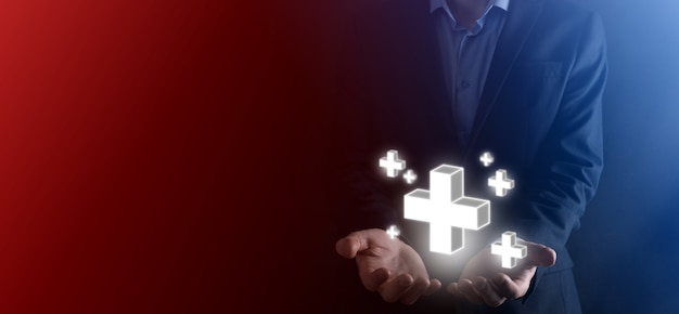 L'uomo d'affari tiene l'icona 3d più, l'uomo tiene in mano offre cose positive come profitto, benefici, sviluppo, csr rappresentato dal segno più. la mano mostra il segno più