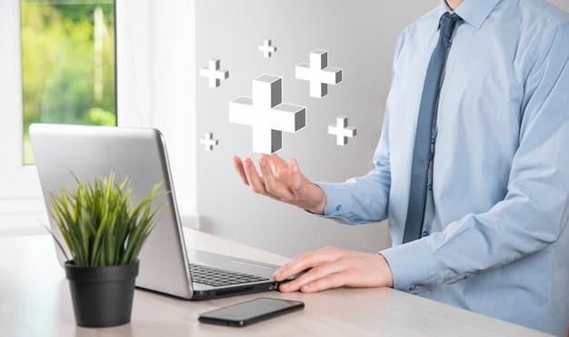 L'uomo d'affari tiene l'icona 3d più, l'uomo tiene in mano offre cose positive come profitto, benefici, sviluppo, csr rappresentato dal segno più.
