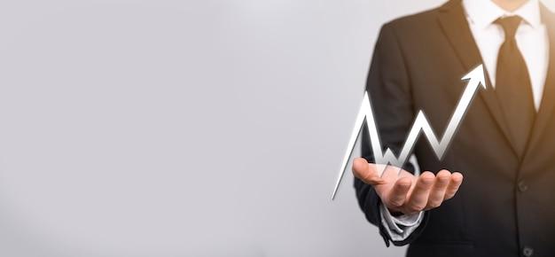 Uomo d'affari tenere disegno sul grafico in crescita dello schermo, freccia dell'icona di crescita positiva. che punta al grafico di affari creativi con frecce verso l'alto.