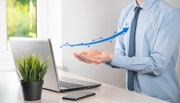 Uomo d'affari tenere disegno sul grafico in crescita dello schermo, freccia dell'icona di crescita positiva. che punta al grafico di affari creativi con le frecce verso l'alto.