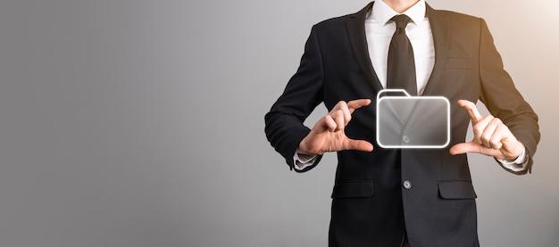 Icona della cartella della tenuta dell'uomo d'affari. sistema di gestione dei documenti o configurazione dms da parte di un consulente it con computer moderno stanno cercando informazioni di gestione e file aziendali. elaborazione aziendale.
