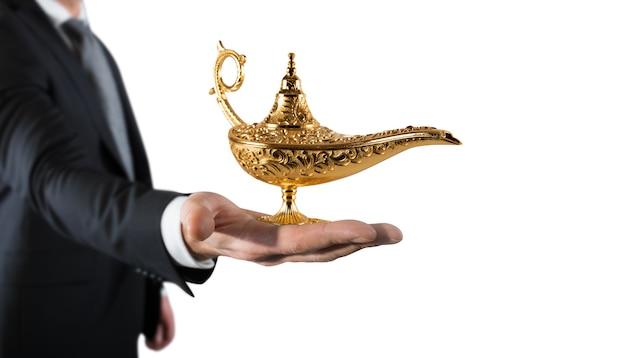 L'uomo d'affari tiene una lampada del genio di aladdin. concetto di desiderio e realizzare un desiderio