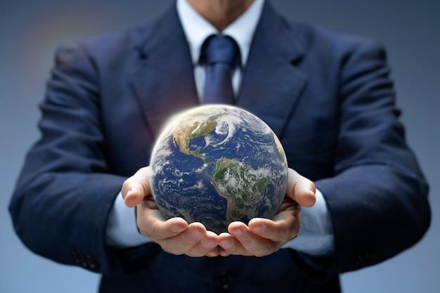 Mondo globale della stretta dell'uomo d'affari. il pianeta terra in mano all'uomo d'affari mostra riscaldamento globale, salva l'ambiente, giornata della terra, rete mondiale, internet, concetto del mondo degli affari. immagine della terra fornita dalla nasa.
