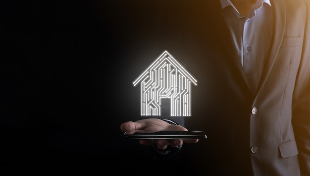 Icona della casa della stretta dell'uomo d'affari concetto di app di automazione domestica controllata, casa intelligente e casa intelligente. pcb design e persona con smart phone. innovazione tecnologia internet network concept.