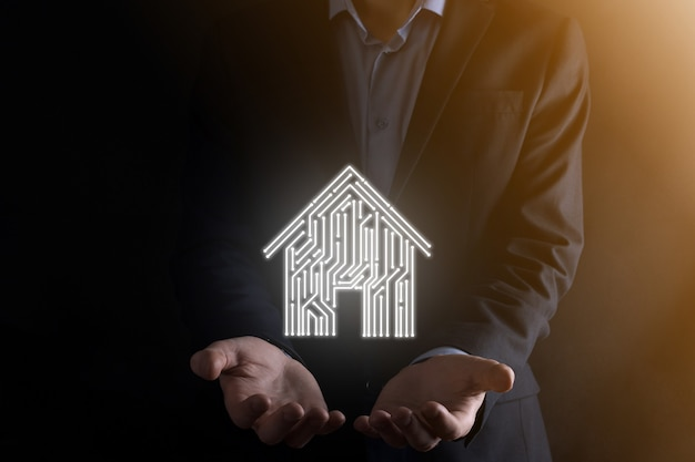 Uomo d'affari tenere icona della casa. casa intelligente controllata, casa intelligente e concetto di app di automazione domestica. progettazione di pcb e persona con smart phone. concetto di rete internet di tecnologia dell'innovazione.