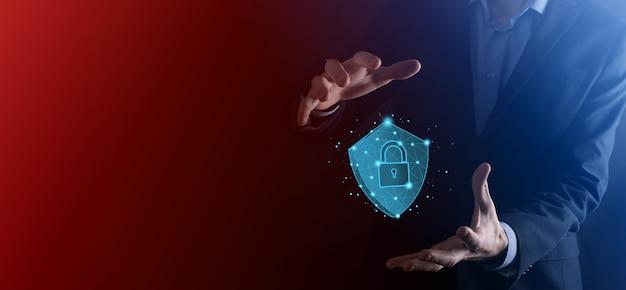 L'uomo d'affari tiene lo scudo poligonale basso con un'icona a forma di lucchetto. concetto di sistema di accesso sicuro. garanzia finanziaria aziendale per gli investimenti. concetto antivirus. sicurezza tecnologica. rete di protezione, dati sicuri.