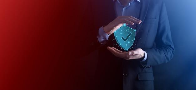 L'uomo d'affari tiene lo scudo poligonale basso con un'icona di spunta. concetto di sistema di accesso sicuro. garanzia finanziaria aziendale per gli investimenti. concetto di antivirus. sicurezza tecnologica. rete di protezione, dati sicuri.