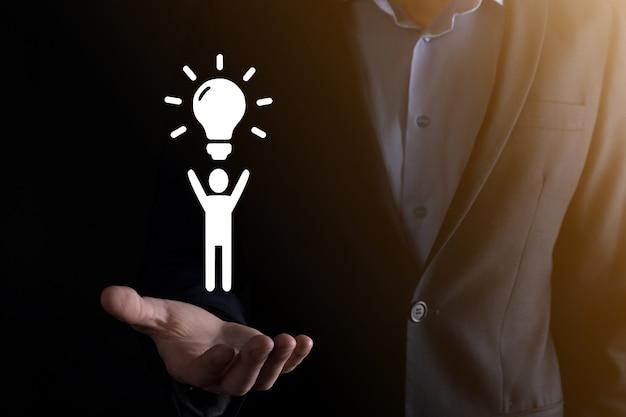 Icona dell'uomo della tenuta dell'uomo d'affari con lampadine, idee di nuove idee con tecnologia innovativa e creatività. creatività concettuale con lampadine che brillano glitter.