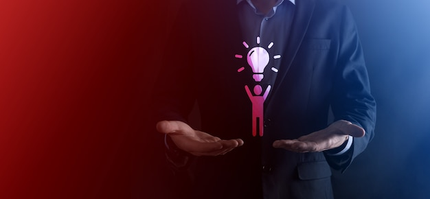 L'uomo d'affari tiene l'icona dell'uomo con lampadine, idee di nuove idee con tecnologia innovativa e creatività. creatività concettuale con lampadine che brillano glitter.