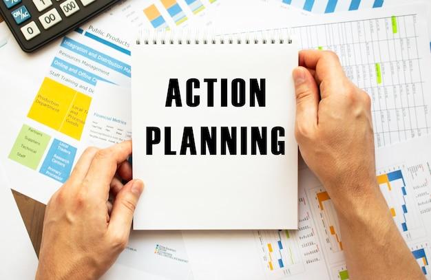 Blocco note della stretta dell'uomo d'affari con la pianificazione dell'azione del testo. grafici finanziari sul desktop. concetto finanziario e aziendale.