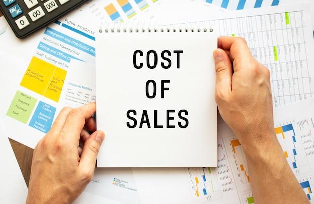 Blocco note della stretta dell'uomo d'affari con il testo costo delle vendite. grafici finanziari sul desktop.