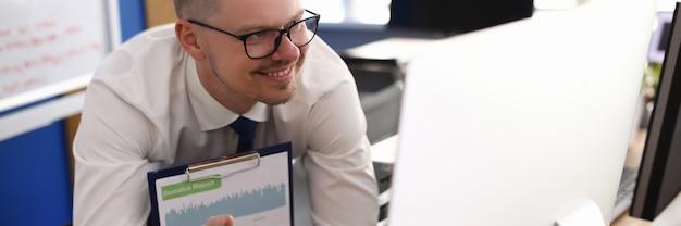 L'uomo d'affari tiene una riunione webinar online tramite il monitor del computer
