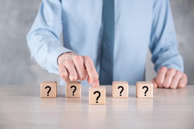 Imprenditore tenere e mettere a forma di blocco cubo di legno con punti interrogativi sul tavolo grigio