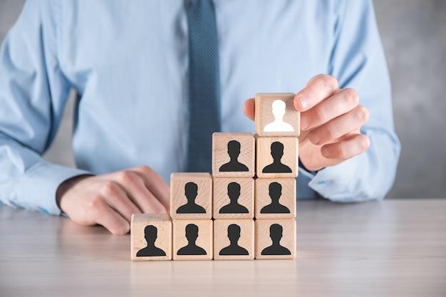 Uomo d'affari tenere e mettere a forma di blocco cubo di legno con l'icona utente sul tavolo grigio. spazio per il testo. primo piano dell'interfaccia delle icone di internet. concetto di media di rete globale, contatto su schermi virtuali, spazio di copia