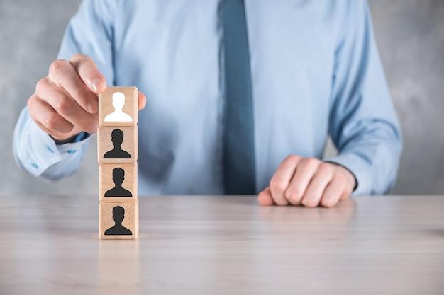L'uomo d'affari tiene e mette a forma di blocco cubo di legno con l'icona dell'utente sul tavolo grigio. spazio per il testo. primo piano dell'interfaccia delle icone di internet. concetto di media di rete globale, contatto su schermi virtuali, spazio di copia