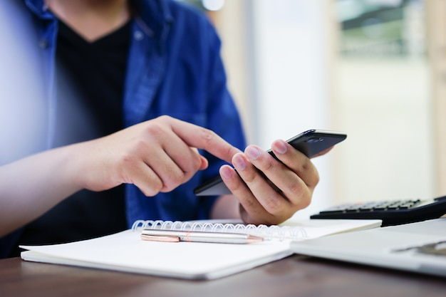 Uomo d'affari tenere telefono intelligente sms e controllare l'email di avviso