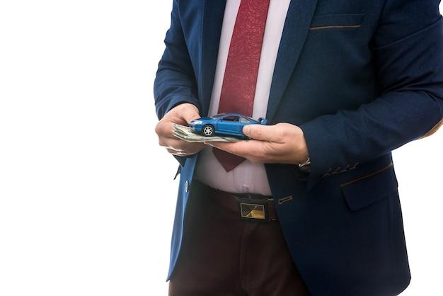 Uomo d'affari tenere macchina giocattolo e noi soldi per la vendita o noleggio auto isolato su bianco