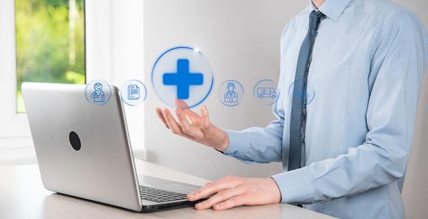 Uomo d'affari tenere icone di connessione di rete virtuale più medica. la pandemia di covid-19 sviluppa la consapevolezza delle persone e diffonde l'attenzione sulla loro assistenza sanitaria. medico, documento, medicina, ambulanza, icona del paziente.