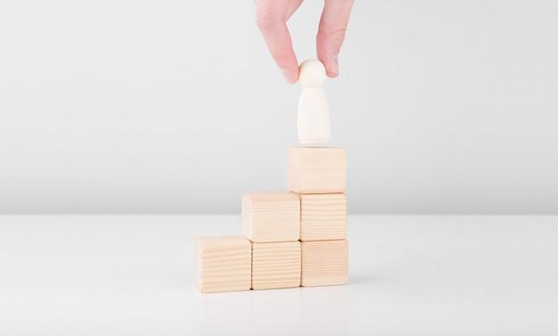 Uomo d'affari tenere l'uomo di legno che rappresenta il leader aumenta il successo con la posizione in piedi in cima alla scala