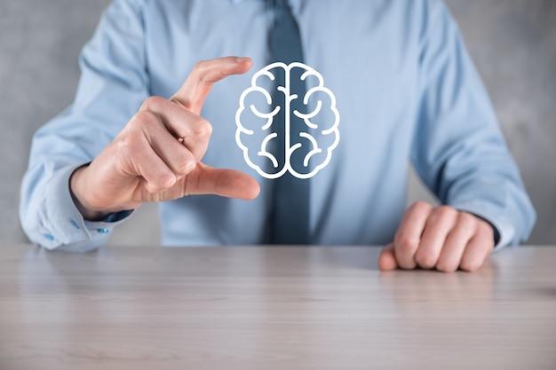 Uomo d'affari che tiene strumenti astratti del cervello e dell'icona, dispositivo, comunicazione della connessione di rete del cliente su tecnologia futura di sviluppo virtuale, innovativo, scienza, innovazione e concetto di business.