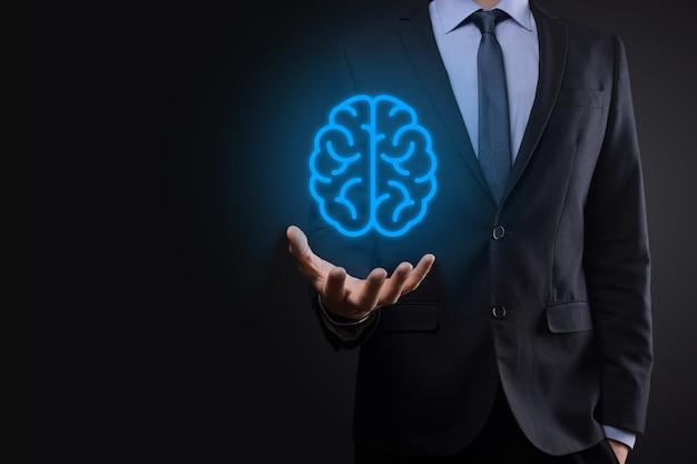 Uomo d'affari che tiene strumenti astratti del cervello e dell'icona, dispositivo, comunicazione della connessione di rete del cliente