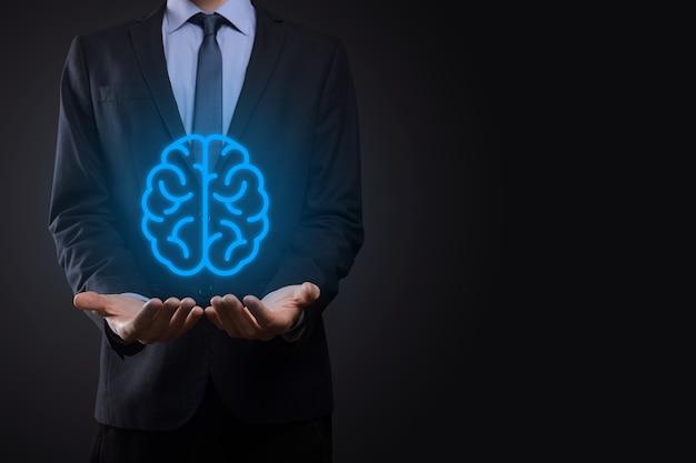 Uomo d'affari che tiene strumenti astratti del cervello e dei simboli, dispositivo, comunicazione della connessione di rete del cliente su tecnologia futura, scienza, innovazione e business di sviluppo innovativo virtuale