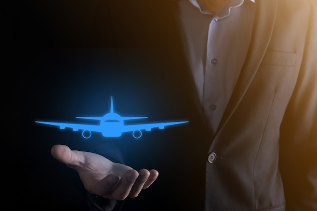 Uomo d'affari che tiene un'icona dell'aeroplano nelle sue mani