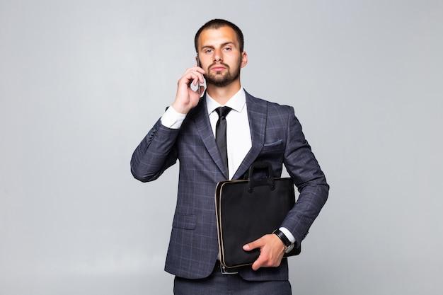 Imprenditore tenendo la borsa a piedi e parlando al telefono su sfondo bianco