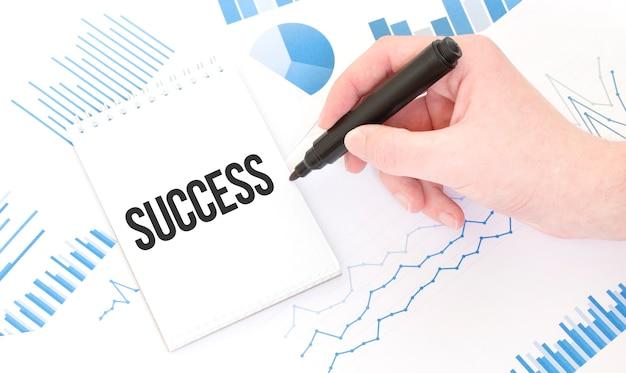 Uomo d'affari che tiene un pennarello nero, blocco note con il testo successo, concetto di affari