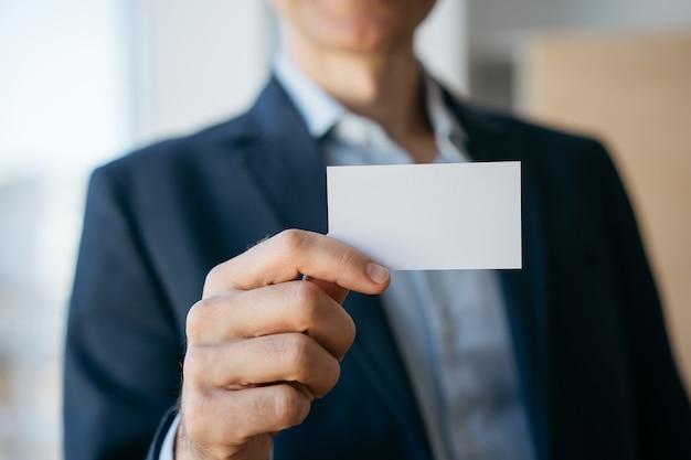 Uomo d'affari che tiene biglietto da visita in bianco