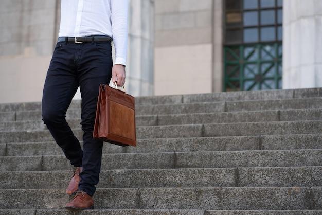Uomo d'affari che tiene una valigetta mentre si cammina giù per le scale. concetto di affari.