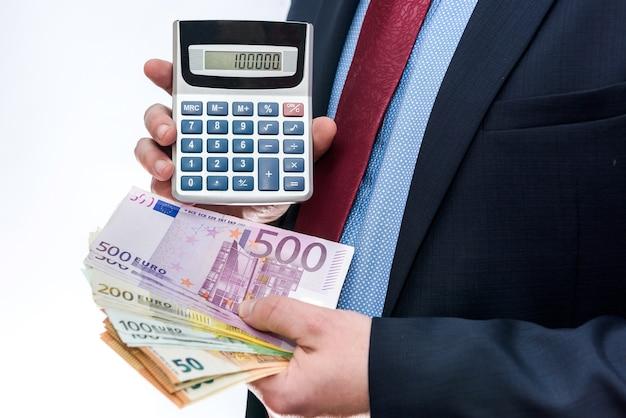 Primo piano del calcolatore e delle banconote in euro della holding dell'uomo d'affari Foto Premium