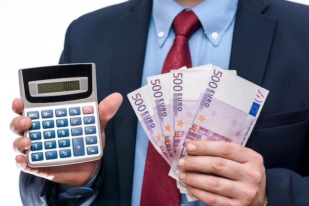 Uomo d'affari che tiene calcolatrice e primo piano delle banconote in euro